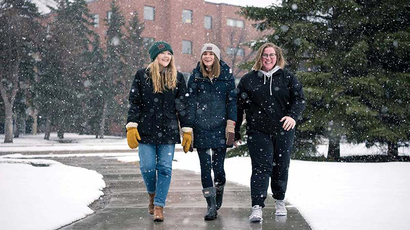 girls walking on campus in snow